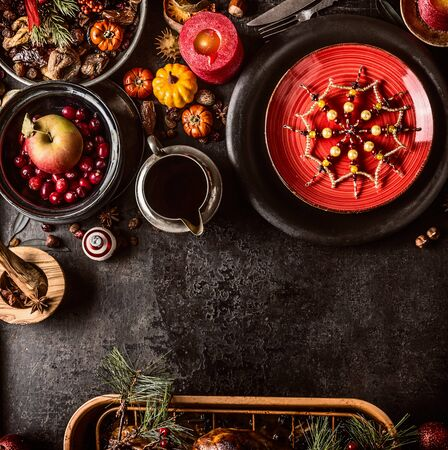 Christmas dinner background with festive table setting, snowflakes decoration, sauce, fresh cranberries and apple, pumpkins, nuts and pine branches. Dark rustic style. Top view. Copy space Zdjęcie Seryjne