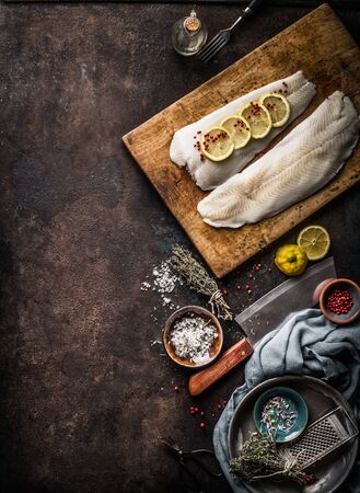 Vertical seafood background with raw cod fillet with lemon slices and herbs on rustic background with cutting board and knife, top view. Fish cooking preparation. Healthy diet food. Copy space