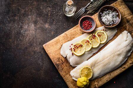 Filetto di merluzzo crudo con fette di limone e sale alle erbe su tagliere di legno rustico su sfondo scuro, vista dall'alto. Preparazione della cottura del pesce. Cibo dietetico sano. Confine. Copia spazio