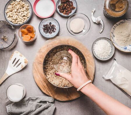 Woman hand making vegan cashew cake on gray concrete background with gluten free ingredients. Top view. Healthy food. Dieting. Vegan cake preparation