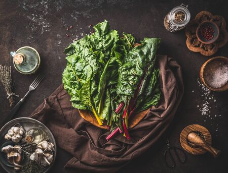 Fresh organic colorful chard leaves bunch on dark rustic table with kitchen utensils, top view. Healthy eating and cooking