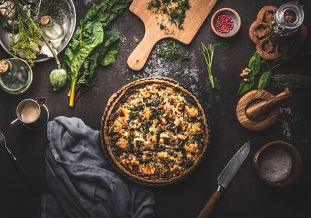 Homemade tasty salmon open faced pie or quiche lorraine on dark rustic table background with kitchen utensils and ingredients, top view