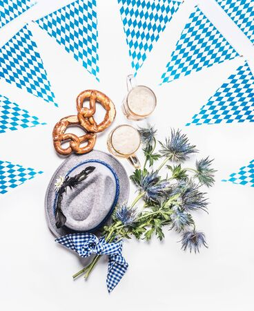 Oktoberfest layout with traditional Bavarian white blue fabric,  pretzel, cups of draft beer, Bavarian hat, party flag garland, decoration and bunch of alpine flowers on white background. Top view. Фото со стока
