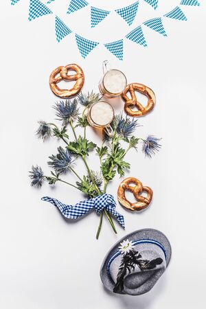 Oktoberfest composition with traditional Bavarian white blue fabric, decoration, pretzel, cups of draft beer, Bavarian hat and bunch of alpine flowers on white background. Top view. Flat lay