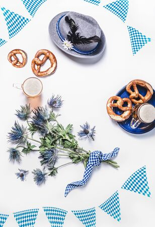 Modern Oktoberfest background with traditional Bavarian white blue fabric, decoration, pretzel, cups of draft beer, Bavarian hat and bunch of alpine flowers. Top view. Flat lay with copy space
