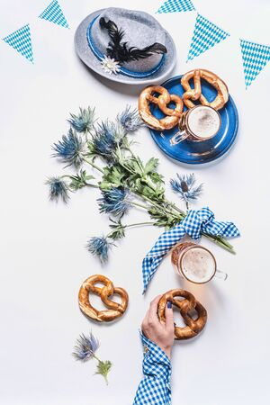 Oktoberfest flat lay in traditional blue colors. Woman hand in traditional shirt holding pretzel on white background with cups of draft beer, Bavarian hat and bunch of alpine flowers. Top view