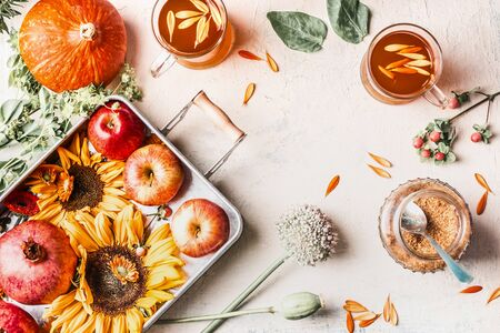Autumn or late summer composition with sunflowers, pumpkin, apples, flowers and herbal tea in glass cups on white desktop. Top view. Copy space. Frame
