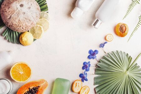 Environmentally friendly vegan cosmetic products on white desk with coconut, fruits, flowers and tropical leaves, top view. Healthy lifestyle . Natural cosmetic layout. Beauty blogging Copy space.