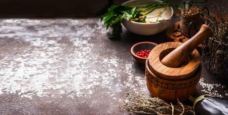 Food  with pestle and mortar, herbs and spices on dark rustic Фото со стока