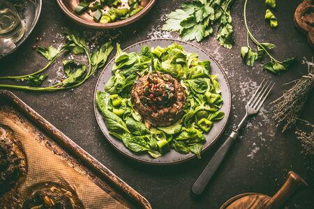 Tasty low carb meal. Minced meat patties made in bagel shape with roasted vegetables served on green salad plate. Top view 스톡 콘텐츠