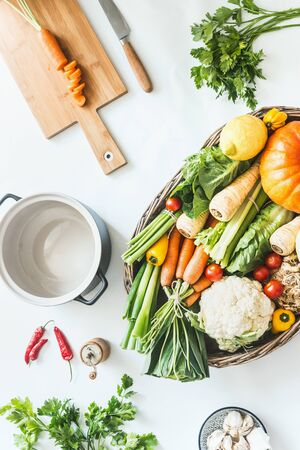 Variety of harvest organic vegetables for tasty seasonal cooking and eating in wooden tray on white kitchen desktop with cutting board, pot, herbs and spices. Top view. Modern healthy lifestyle. Blog