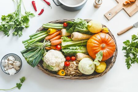 Various harvest organic vegetables for tasty cooking and eating in wooden tray on white desktop with kitchen utensils herbs and spices, top view. Healthy lifestyle. Local vegetarian food. Zero waste Stock fotó
