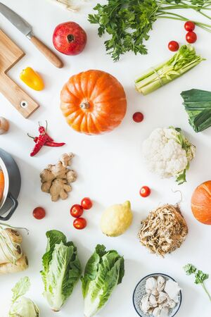 Healthy organic seasonal vegetables on white kitchen desktop with herbs and spices. Top view. Frame. Copy space. Vegetarian cooking and eating.  Local food. Blog layout. Pumpkin time.