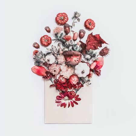 Envelope with autumn floral arrangement on white desk background. Creative fall ideas. Blog layout. Autumn objects of nature. Top view. Flat lay Stockfoto