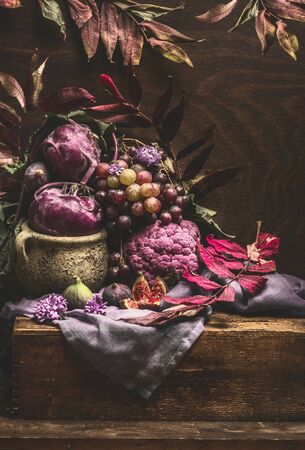 Still life with purple fruits and vegetables on wooden table with crockery, napkin and autumn leaves . Copy space for your design Archivio Fotografico