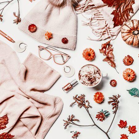 Plat d'automne féminin avec pull tricoté, chapeau, lunettes de lecture, tasse de cappuccino, écharpe, maquillage, citrouilles et fleurs séchées. Vue de dessus. Mise en page du blog. Style Instagram. Mode et beauté