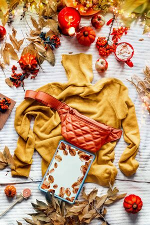 Empty screen tablet on yellow knitted sweater with orange waist bum bag. Cup of coffee with candle, pumpkins and autumn leaves. Fall fashion clothes. Cozy day outfit. Flat lay. Top view. Blog layout