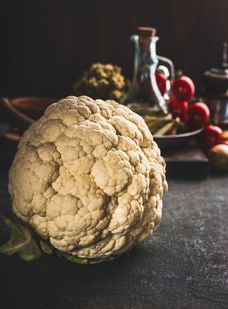 Close up of whole cauliflower on dark rustic kitchen table background. Copy space Reklamní fotografie