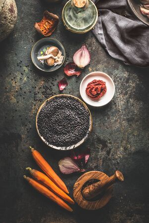 Black lentils with cooking ingredients for tasty vegan dishes on dark background. Top view. Healthy vegetarian eating concept. Horizontal banner. Plant based protein source. Top view Zdjęcie Seryjne - 133496484