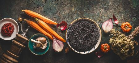 Black lentils with cooking ingredients, vegetables, herbs and spices for tasty vegan meals on dark background. Top view. Healthy vegetarian eating concept. Horizontal banner. Plant based protein