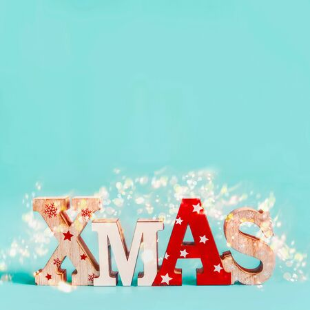 Word Xmas with copy space and holiday bokeh on blue background. Festive Christmas concept. Greeting card, invitation or sale layout