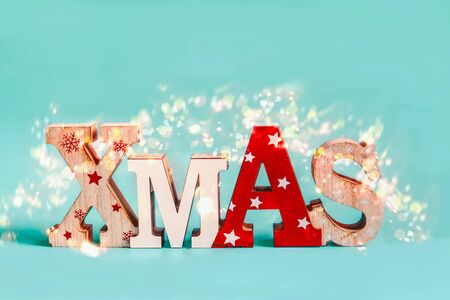 Word Xmas with holiday bokeh on blue background. Festive Christmas concept. Greeting card layout