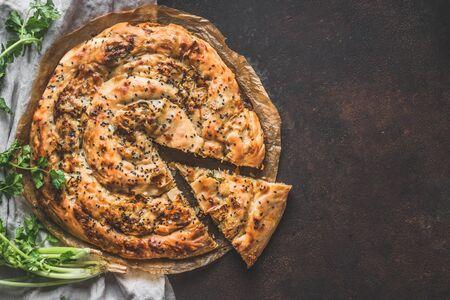 Turkish savory pie with Phyllo dough. Su boregi, burek or borek on dark rustic background. Top view.