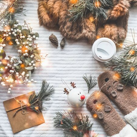 Cozy winter flat lay with fur blanket, funny socks, cedar branches, wreath, Christmas toys and greeting envelope with led string lights bokeh. Top view. Frame. Copy space