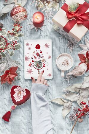Female hand using tablet computer with Christmas tree greeting card on light blue knitted blanket with red vintage Christmas decoration, present gift box, burning candles and  cup of cappuccino .
