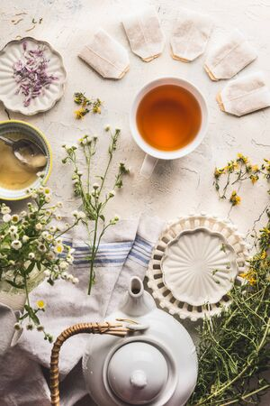 Cup of herbal tea with tea bags , teapot with fresh medical herbs and honey on white table, top view. Healthy lifestyle concept