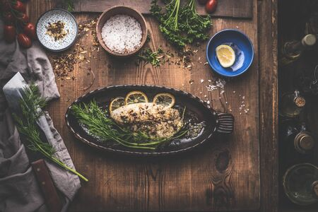 Fish fillet with lemon and  herbs in backing pan on rustic kitchen table background with ingredients. Top view