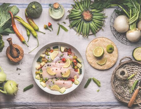 Fish cooking preparation with raw god fish fillet in white cooking pan on rustic table with various vegetables, top view.  Healthy low carb dieting food