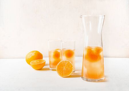 Refreshing lemonade with fruits ice cubes of orange juice in jug and glasses on white table
