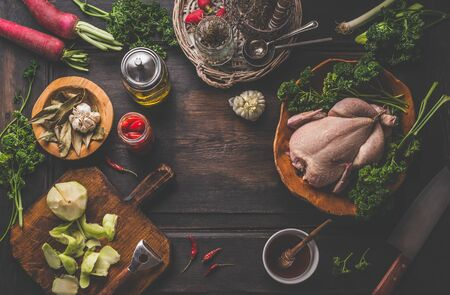 Food background with raw whole chicken on dark rustic kitchen table with ingredients for tasty home cooking. Preparation and chicken marinating with lemon, honey and  mustard. Home cuisine. Top view