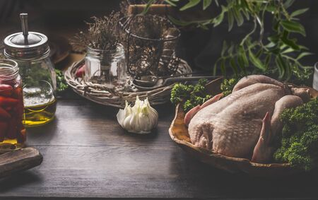 Raw whole chicken on dark rustic background with ingredients for tasty home cooking. Preparation and chicken marinating with lemon, honey and  mustard. Home cuisine. Chicken soup or broth cooking Zdjęcie Seryjne