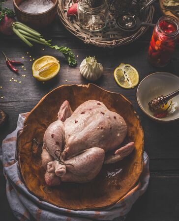 Close up of raw whole chicken on dark rustic background with ingredients for tasty home cooking. Preparation and chicken marinating with lemon, honey and  mustard. Home cuisine. Top view
