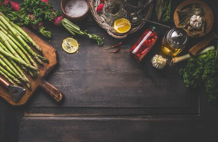 Dark food background with green asparagus and various ingredients and jars with preserved vegetables, seasoning and kitchen tools for tasty home cooking. Top view. Place for your design or product