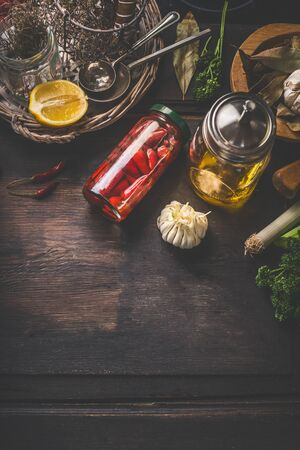 Food background with pickled vegetables, jar with olives oil, herbs and spices on dark kitchen table. Top view. Home cuisine. Tasty cooking and preserving Zdjęcie Seryjne
