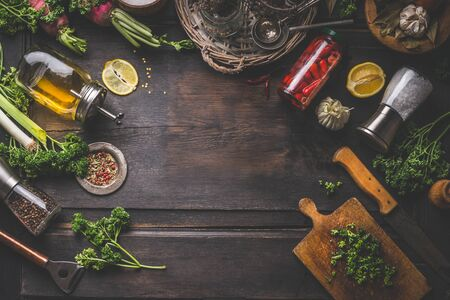 Dark food background with various ingredients and jars with preserved vegetables, seasoning and kitchen tools for tasty home cooking. Top view. Place for your design or product. Frame Zdjęcie Seryjne