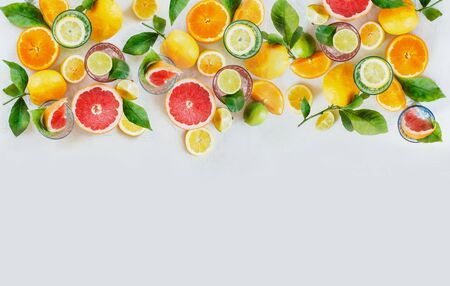 Various colorful citrus fruits: lemon, lime, orange and grapefruit with green leaves and glasses of refreshing lemonade drinks on white background, top view. Healthy lifestyle. Border or frame.