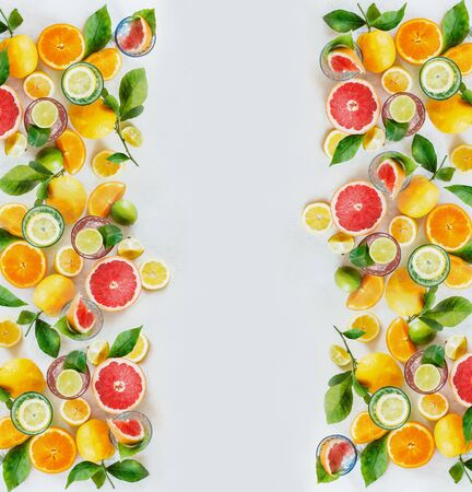 Frame of various colorful citrus fruits: lemon, lime, orange and grapefruit with green leaves and glasses of refreshing lemonade drinks on white background, top view. Healthy lifestyle. Layout.