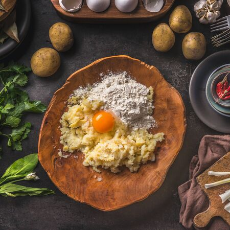 Gnocchi dough ingredients. Potatoes with egg and flour in wooden bowl on dark kitchen table with organic ingredients for tasty home cooking. Food preparation. Frame. Top view. Vintage cuisine Zdjęcie Seryjne