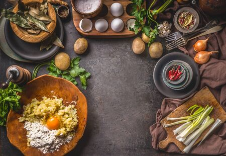 Rustic food background with preparation of potato dough . Mashed potatoes with egg and flour in wooden bowl . Dark kitchen table with organic ingredients for tasty home cooking.  Frame. Top view.