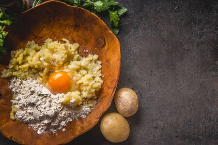 Food background with preparation potato  dough. Potatoes with egg and flour in wooden bowl on dark kitchen table with ingredients. Tasty home cooking.   Top view. Copy space