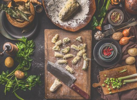 Homemade gnocchi preparation. Potatoes dough on dark rustic kitchen table with cutting board and healthy ingredients. Tasty home cuisine. Top view. Still life