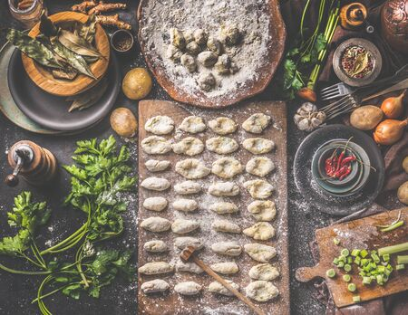 Homemade gnocchi making preparation. Potatoes dough on dark rustic kitchen table with cutting board and healthy ingredients. Tasty home cuisine. Top view. Still life Zdjęcie Seryjne