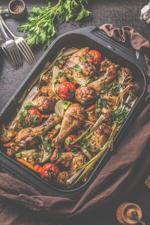 Roasted chicken and vegetables in black grill frying pan on rustic table background with ingredients. Top view Zdjęcie Seryjne