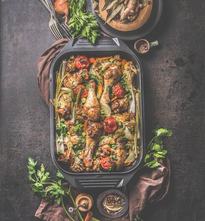 Oven roasted chicken and vegetables in black grill frying pan with herbs and spices on rustic background . Top view