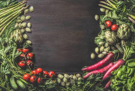 Food background with group of various fresh organic vegetables from garden on dark rustic wooden background. Top view. Healthy clean vegetarian ingredients: Tomato, lettuce, root vegetables,artichokes Zdjęcie Seryjne