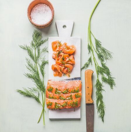 Homemade smoked salmon fillet with dill and lemon served on marble cutting board on light background. Top view. Healthy food. Tasty home cuisine